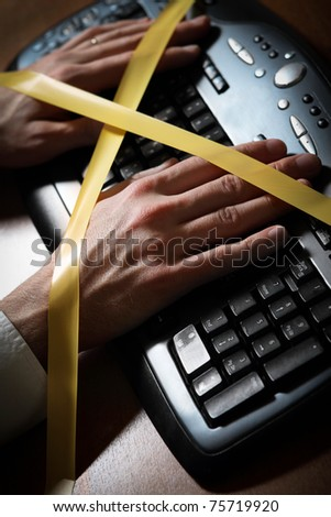 Close-up of a man's hand with duct tape typing at a computer keyboard