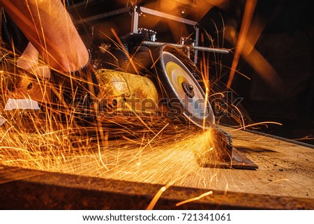 Close-up of a man sawing metal with a hand circular saw on a wooden table in the workshop