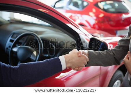 Close up of a man shaking hand to a woman in a dealership