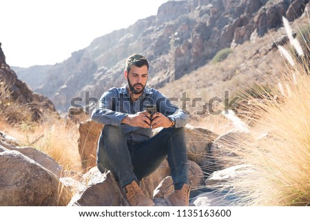 Close up of a man sitting on a rock in the mountains texting on a cell phone