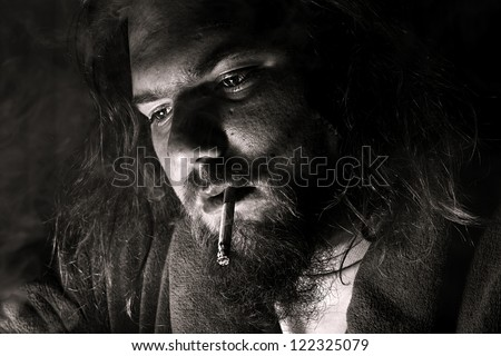 close up of a man smoking a cigarette with dramatic lighting