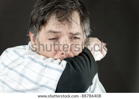 Close-up of a man stifling a sneeze in his elbow.