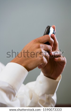 Close up of a man using a mobile phone to SMS test message
