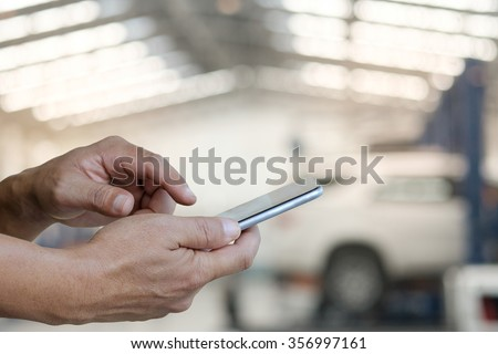 Close up of a man using mobile smart phone in garage background. #356997161