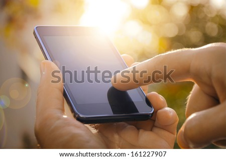 Shutterstock Close up of a man using mobile smart phone outdoor