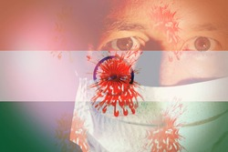 Close up of a man wearing a mask with a fear expression, with an Indian flag and virus cells as background. Concept of Corona Virus India.