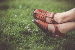 Close up of a man wearing genuine Sandal leather shoes or vintage leather sandal shoe on the grass. Palestine HEBRON LEATHER industry sandals shoe