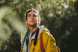 Close up of a man wearing jacket and backpack on an exploration trail. Side view portrait of a traveler standing outdoors looking away.