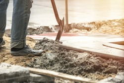 Close up of a man worker using a hoe to plastering cement concrete on a sidewalk at worksite construction.