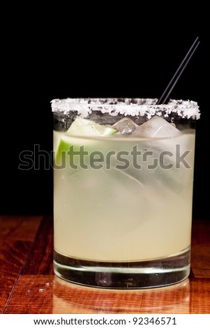 close up of a margarita garnished with a fresh lime and a salt rim around the glass