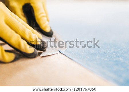 Close-up of a master professionally and professionally performs the cutting of PVC cord after hot welding homogeneous commercial linoleum