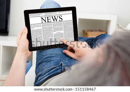 Close-up Of a Mature Man reading news on digital tablet