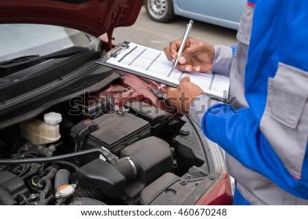 Close-up Of A Mechanic With Clipboard Checking Car Engine #460670248