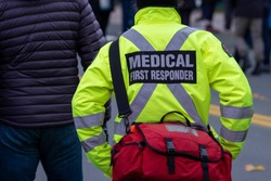 Close up of a medical first responder wearing a bright yellow coat with a grey reflective cross. The person is back on to the camera. There are people in the street in the background of the photo.