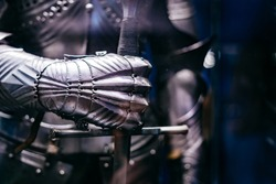 Close up of a Medieval steel armour with hand holding a giant sword