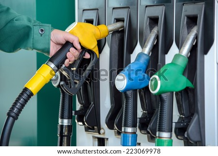 Close-up of a men\'s hand using a fuel nozzle at a gas station. Petrol station. Filling station. Petrol. Gasoline.