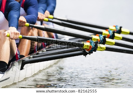 Close up of a men's quadruple skulls rowing team, seconds after the start of their race - stock photo