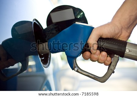 close-up of a mens hand refilling the car with a gas pump