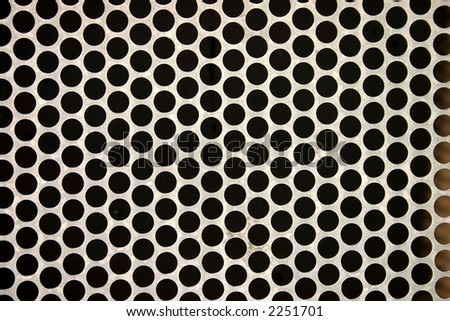 Close up of a metal fence with round holes, makes an interesting abstract background.