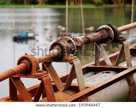 close up of a metal steel drive shaft of a water pump on a large size ball bearing support and universal joint with dark dirty grease with shrimp farm water surface in the background.