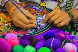 Close up of a Mexican man working of his handcraft with bokeh of yarn in front.