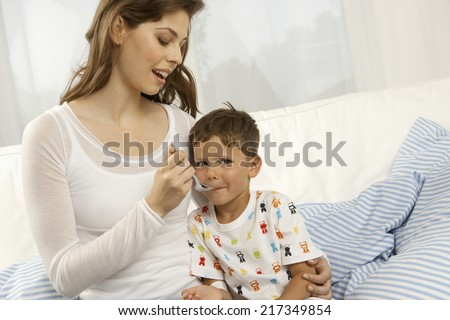 Close-up of a mid adult woman giving medicine to her son