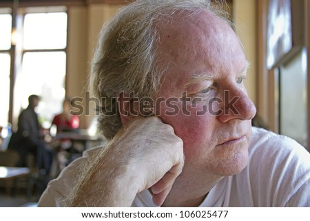 Close up of a middle aged man alone in thought in a restaurant - stock photo