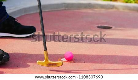 Close-up of a miniature golf putter and a pink golf ball and pink golf ball