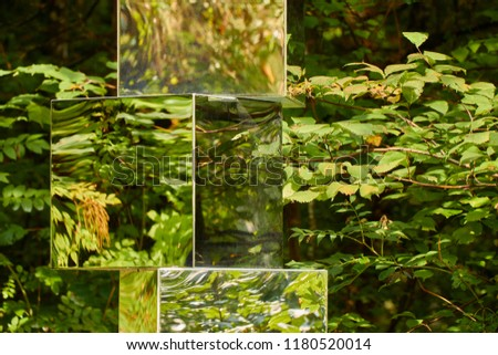 Close up of a mirror statue with green reflected tree leaves near Hallstatt salt mines in Austria.  #1180520014