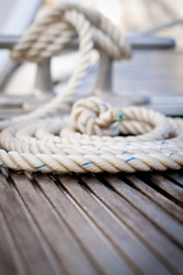 Close-up of a mooring rope with a knotted end tied around a cleat on a wooden pier/ Mooring rope