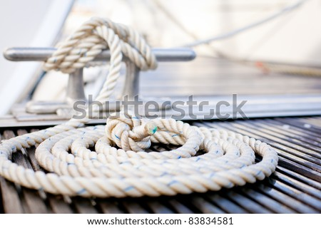 Close-up of a mooring rope with a knotted end tied around a cleat on a wooden pier/ Nautical mooring rope #83834581