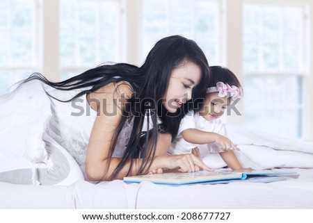 Close-up of a mother and baby girl reading book story on bed