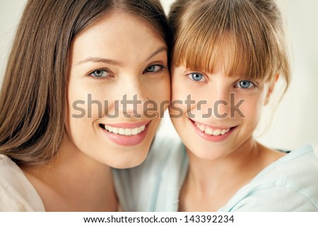 Close-up of a mother and her cute daughter smiling and posing.
