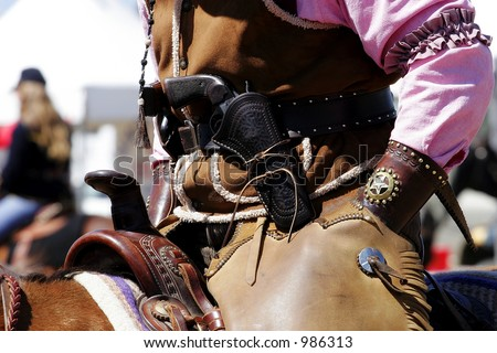 Close-up of a mounted rider with Old West period correct clothing and revolver.