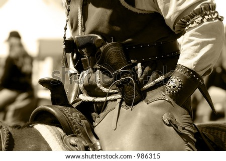 Close-up of a mounted rider with Old West period correct clothing and revolver (sepia/vintage tone).