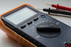 Close-up of a multimeter on a light background. Detailed shot of a measuring device. Qualified electrician services. Selective focus.