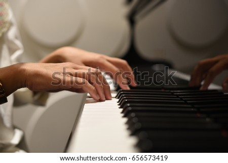 Close-up of a music performer's hand playing the piano #656573419
