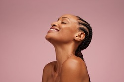 Close-up of a natural beauty smiling on pink background. Woman with beautiful skin having braided hair smiling and eyes closed.
