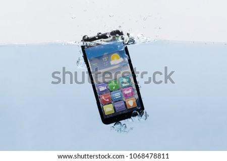 Close-up Of A New Black Mobile Phone Submerged In Water #1068478811