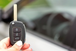 Close-up of a new modern automobile key in woman's hand on the background of a silver car. The concept of buying new auto and car loans. Backdrop for advertising with copy space.