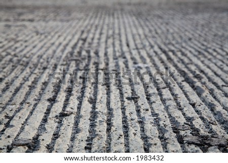 Close up of a newly constructed freeway surface with parallel lines and debris