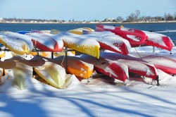 Close up of a number of colorful canoes stored on shore, covered with fresh fallen snow on a sunny winters day