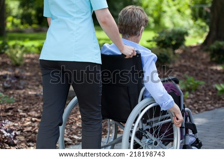 Close-up of a nurse pushing elderly woman on wheelchair