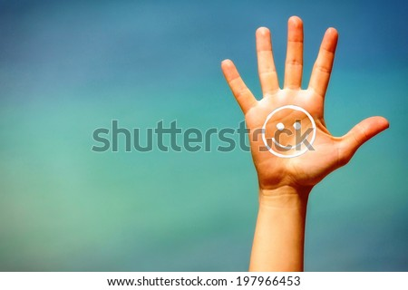 Close up of a open hand, with suncream on it, on blue background.