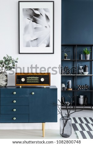 Close-up of a painting, blue cabinet, retro radio and glass vase with branches in dark living room interior and metal shelf in the background