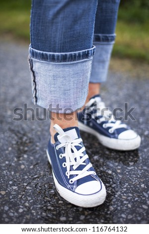 Close up of a pair of blue sneakers and blue jeans on a wet ground