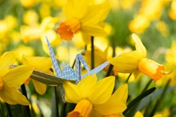 Close-up of a paper origami crane sitting on grass between blossoming early bloomers symbolizing spring time, a fresh start and hope