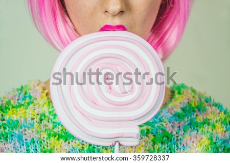 Stock Photo Close up of a part of girl's face and an lollipop that she's holding-fashion and beauty concept