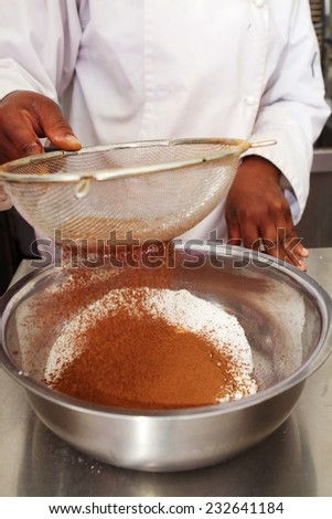 Close up of a pastry chef sifting cocoa into flour mix
