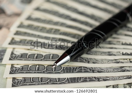 Close up of a pen on the background of dollars
